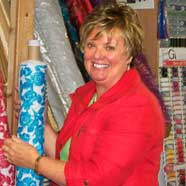 Shop owner, Elizabeth Shirley in amongst the fabrics.