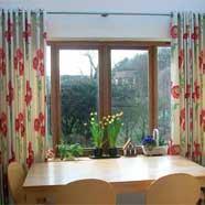 Solar ring headings on full-length curtains made by Victoria Fabrics in Wotton-under-Edge.